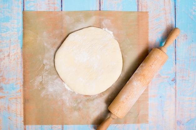 Rolo de madeira sobre a massa plana sobre o papel de pergaminho na mesa de madeira
