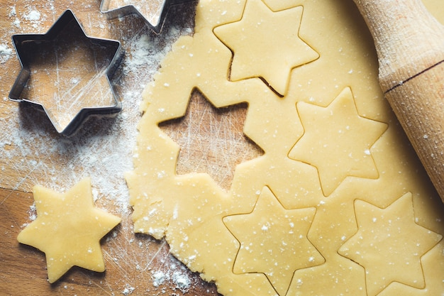 Rolo de massa cortador de biscoitos canela farinha ovos massa de manteiga na madeira