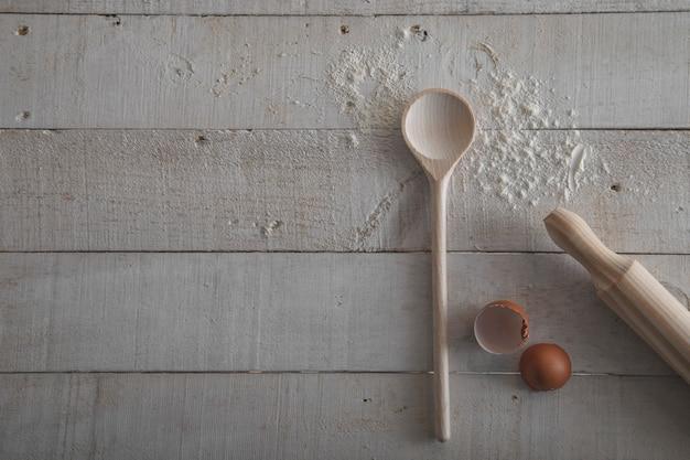 Rolo de massa e colher de pau para fazer massa, farinha e ovo em fundo branco de madeira.