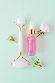 Rolo de massagem de quartzo para o rosto de nefrite natural rosa com soro de beleza ou óleo essencial de rosa. massagem facial cuidados com a pele e relaxamento. ferramentas de massagem em casa. procedimentos anti-envelhecimento e levantamento.