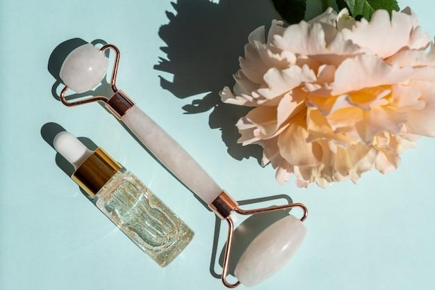 Rolo de massagem facial feito de quartzo rosa com frasco de soro ouro 24k sobre fundo azul. o conceito de cuidados com a pele em casa.