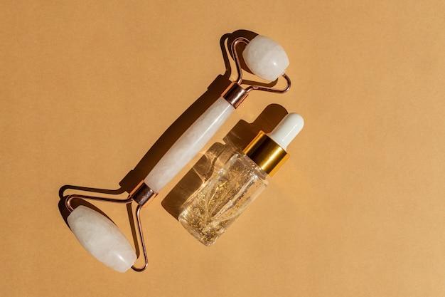 Rolo de massagem facial feito de quartzo rosa com frasco de soro ouro 24k sobre fundo bege. o conceito de cuidados com a pele em casa.