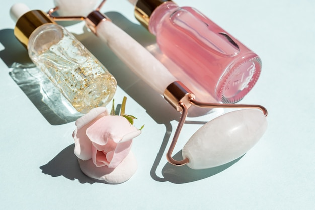 Rolo de massagem facial feito de quartzo rosa com frascos de óleo cosmético ou soro sobre fundo azul. o conceito de cuidados com a pele em casa. soro ouro 24k e água de rosas para tratamento facial.