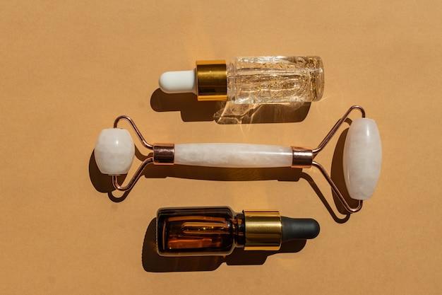 Rolo de massagem para o rosto feito de quartzo rosa com frasco de óleo essencial de final de soro ouro 24k sobre fundo bege. o conceito de cuidados com a pele em casa.