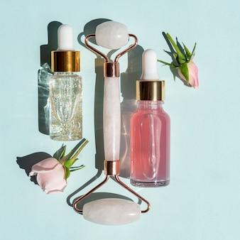 Rolo de massagem para o rosto feito de quartzo rosa com frascos de óleo cosmético ou soro sobre fundo azul. o conceito de cuidados com a pele em casa. soro ouro 24k e água de rosas para tratamento facial.