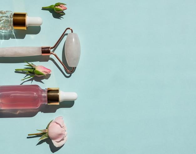 Rolo de massagem para rosto feito de quartzo rosa com frascos de óleo cosmético ou soro sobre fundo azul