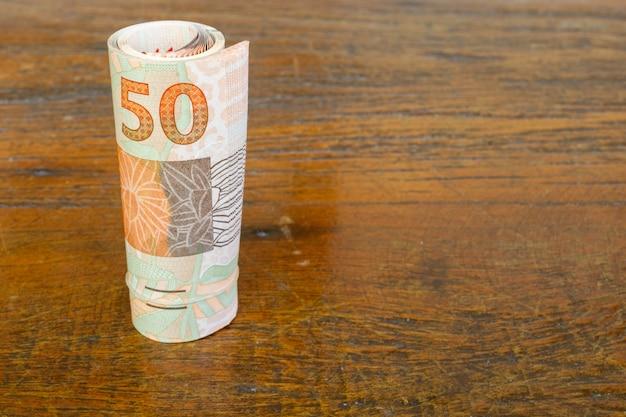 Rolo de notas de dinheiro brasileiro na mesa