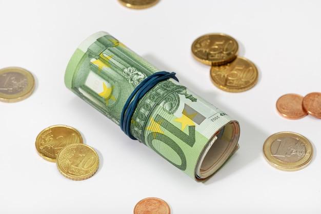 Rolo de notas de euro com elástico e moedas isoladas no fundo branco. conceito de dinheiro