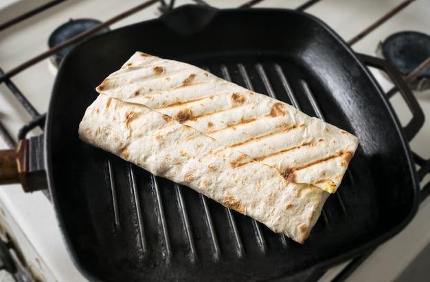 Rolo de pão pita em uma frigideira.