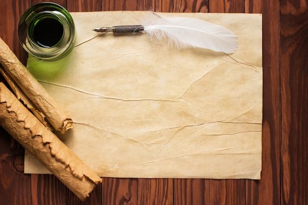 Rolo de papel com caneta de pena e tinteiro no fundo de madeira