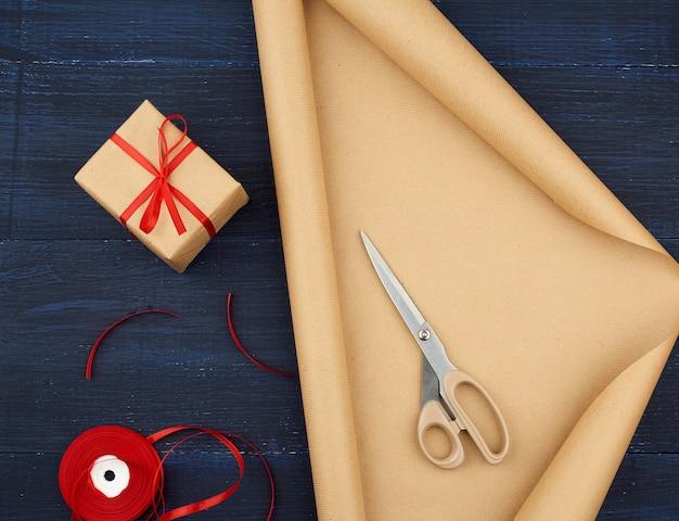 Rolo de papel de embalagem kraft marrom, caixa amarrada com uma fita de seda vermelha