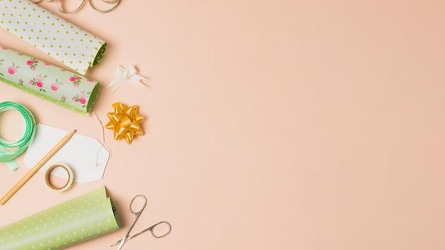 Rolo de papel de embrulho; fita adesiva; lápis; arcos de fita e tesoura, dispostos em superfície de pêssego com espaço para texto