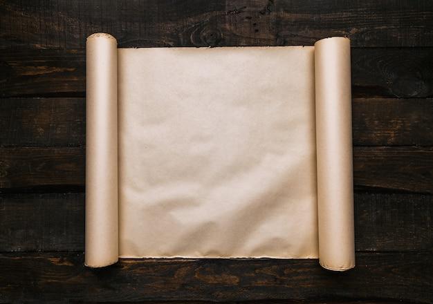 Rolo de papel envelhecido velho no fundo de pranchas de mesa de madeira escura. conceito criativo de aventura plana leiga busca. espaço para texto, cópia, rotulagem.