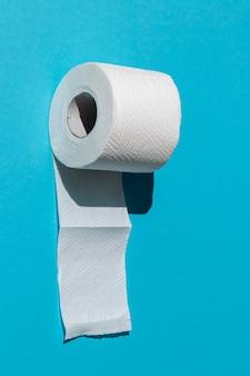 Rolo de papel higiênico branco isolado em um close-up de fundo azul