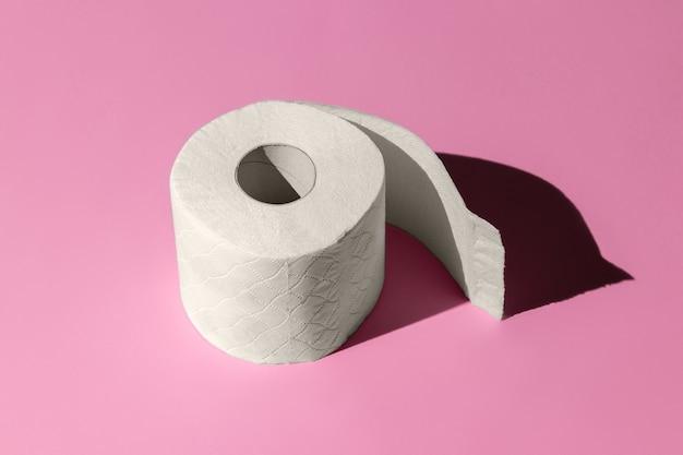 Rolo de papel higiênico branco isolado em um close-up de fundo rosa. sombras duras do sol ao meio-dia