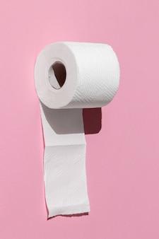 Rolo de papel higiênico branco isolado em um close-up de fundo rosa