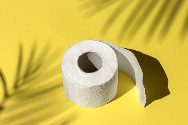 Rolo de papel higiênico branco isolado em um fundo amarelo sob a sombra de uma palmeira