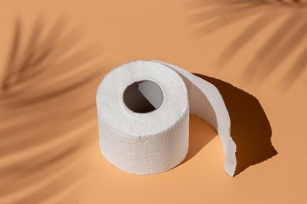 Rolo de papel higiênico branco isolado em um fundo de cor de areia sob a sombra de uma palmeira