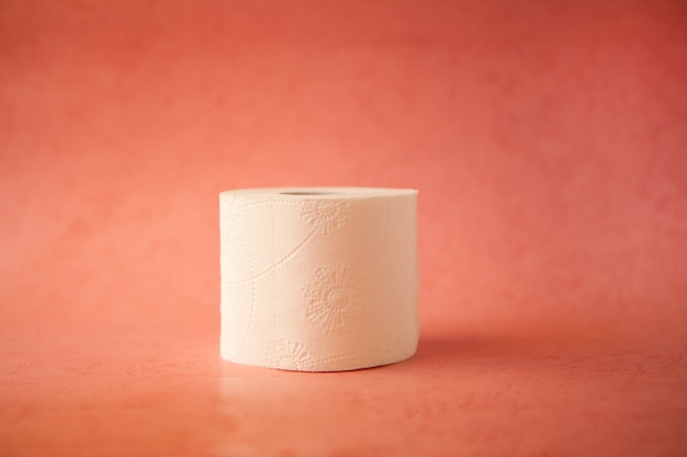Rolo de papel higiênico branco macio em fundo rosa pastel brilhante conceito de higiene e crise
