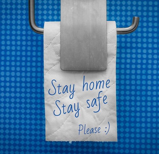 Rolo de papel higiênico branco sobre fundo de parede azul com o texto fique em casa, fique seguro