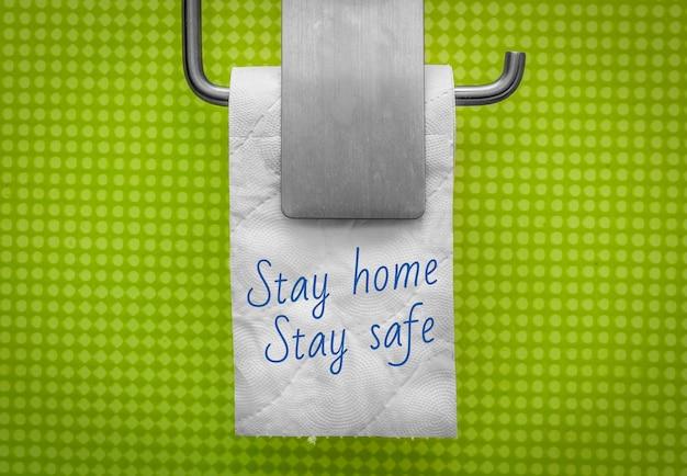 Rolo de papel higiênico branco sobre fundo de parede verde com o texto fique em casa, fique seguro