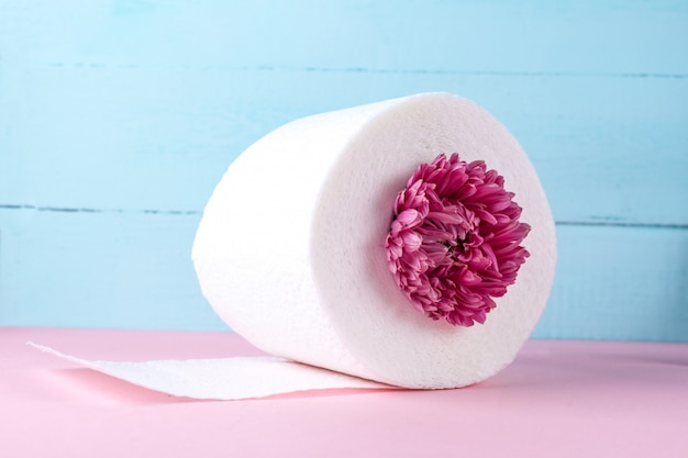 Rolo de papel higiênico com sabor e uma flor rosa em uma mesa rosa. papel higiênico com um cheiro. conceito de higiene