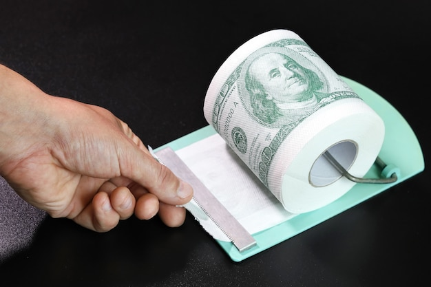 Rolo de papel higiênico em forma de dólares com a mão segurando a borda desbloqueada em fundo preto
