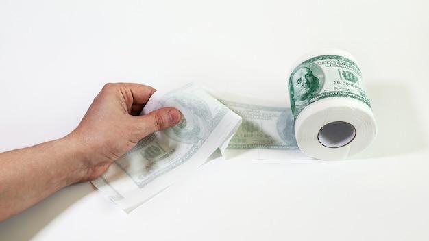 Rolo de papel higiênico em forma de dólares com a mão segurando a borda destravada