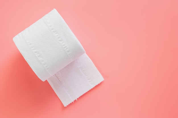 Rolo de papel higiênico ou tecido em fundo rosa