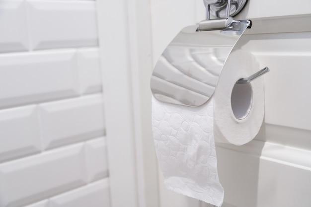 Rolo de papel higiênico pendurado no banheiro de perto