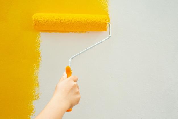 Rolo de pintura amarelo na parede da casa sozinho para decorar a casa.
