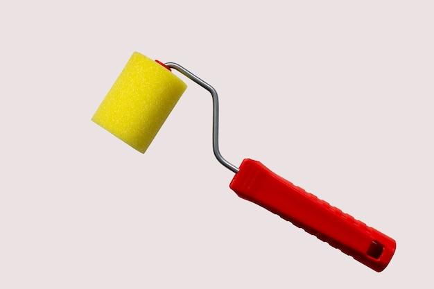 Rolo de pintura de espuma amarela e cabo vermelho