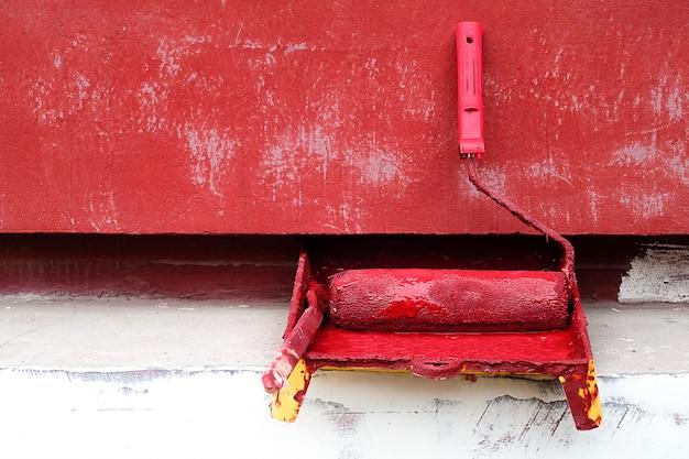 Rolo de pintura e pincel com tinta vermelha perto da parede pintada do edifício. o conceito de reparação profissional, construção, restauração.
