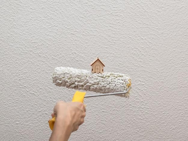 Rolo de pintura e uma casa de brinquedo. o conceito de renovação no apartamento.