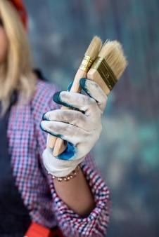 Rolo de pintura na mão feminina perto da parede colorida. renovação