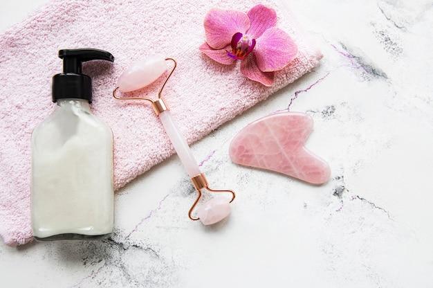 Rolo de rosto de jade para terapia de massagem facial de beleza com toalha e flores de orquídea.