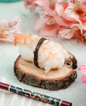 Rolo de sashimi em um pedaço de madeira.