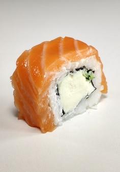 Rolo de sushi bonito de filadélfia na parede branca.