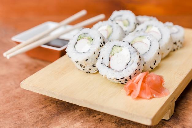 Rolo de sushi califórnia com molho de soja em uma mesa de madeira