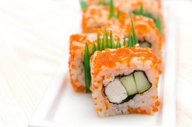Rolo de sushi caseiro com vara de caranguejo e pepino em chapa branca.