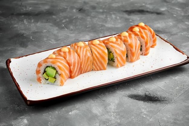 Rolo de sushi clássico dragão vermelho com abacate, salmão, omelete e molho picante em um prato branco sobre uma mesa cinza. foco seletivo, granulação de ruído na postagem