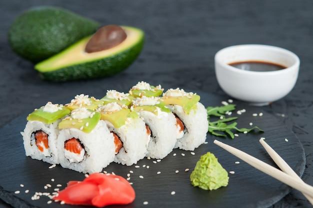 Rolo de sushi com abacate no fundo preto.