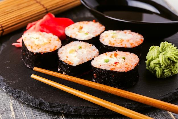 Rolo de sushi com caranguejo, molho picante, pepino e caviar tobiko.