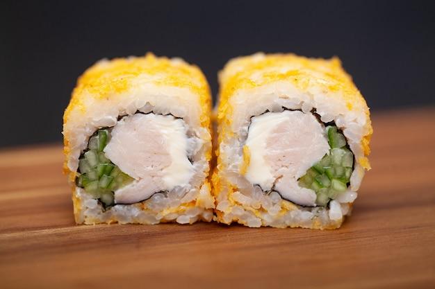 Rolo de sushi com frango, queijo e pepino.