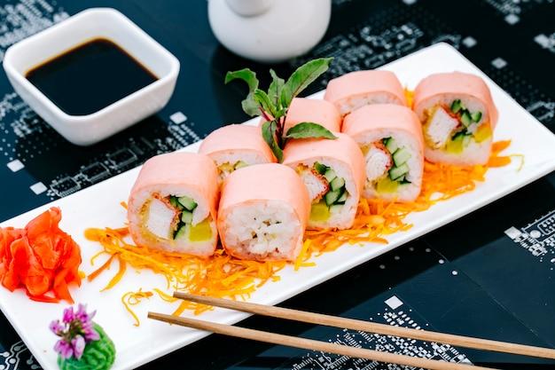 Rolo de sushi com palitos de caranguejo, pepino e pimentão, servido com molho de soja, gengibre e tempura