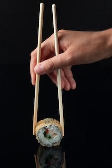 Rolo de sushi com reflexo em um fundo preto. restaurante com culinária japonesa. mãos femininas segurando rolos de sushi