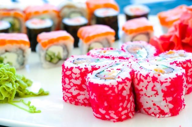 Rolo de sushi comida japonesa no restaurante. ovas de peixe voador vermelho. sushi próximo acima no prato branco.