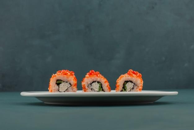 Rolo de sushi da califórnia com caviar na mesa azul.