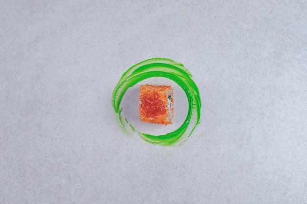 Rolo de sushi da califórnia em fundo branco com anel de plástico verde.