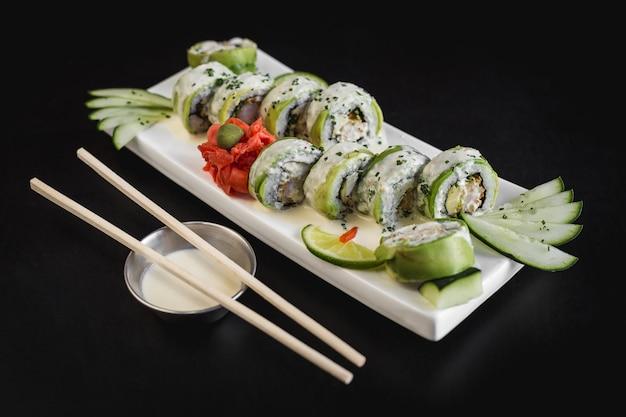 Rolo de sushi de abacate e queijo com molho de ceviche em uma mesa preta